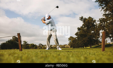 Low angle shot of senior male golfer taking shot while standing on field. Full length of golf player swinging golf club. - Stock Photo