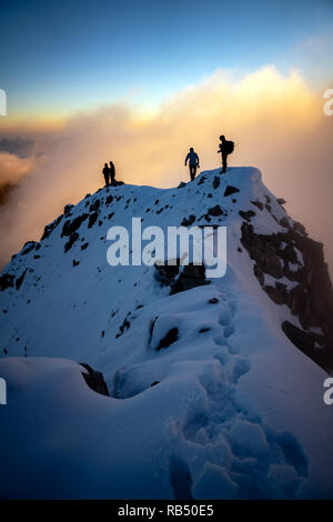 Kaprun, Austria - September 6, 2018. A group of mountaineers are overlooking the valleys from the peak of the Grosses Wiesbachhorn at sunrise. The Grosses Wiesbachhorn is part of Hohe Tauern mountain range in the Salzburg region. - Stock Photo