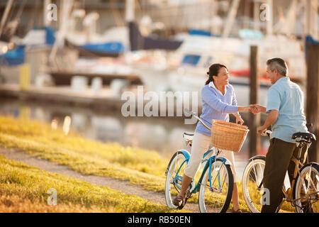 Middle aged couple hold hands and look at each other while riding bicycles at a boat marina. - Stock Photo