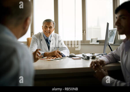 Senior doctor consulting with patients in his office. - Stock Photo