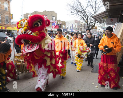 Troupe performs Lion Dance to bring good luck and prosperity to Chinese owned stores in the Bensonhurst section of Brooklyn on Chinese New Year, 2017. - Stock Photo