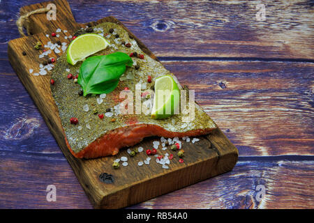 Raw rainbow trout steak sprinkled with spices, pepper, salt with pieces of lime and basil leaves on an old wooden board. Flat view from above in vinta - Stock Photo