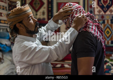Portrait of a bedouin Arabic man helping another with wearing a head scarf bedouin style in Siwa Egypt - Stock Photo