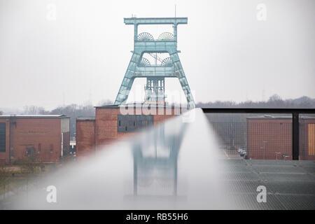 Der Förderturm der Zeche Ewald spiegelt sich in einem Geländer. - Stock Photo