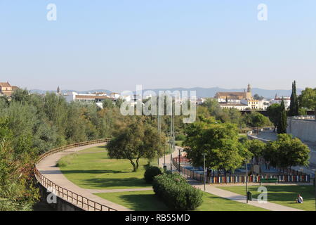 A view of the other bank of the river in Cordoba presenting the opposite side to the Mezquita, showing a local park and promenade - Stock Photo