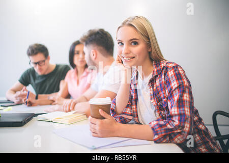 Cheerful young blonde woman look on camera and smile. She hold one hand under chin. Her teammakers work together behind her. - Stock Photo