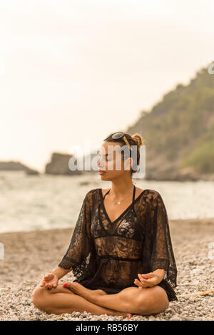 Female wearing black lace tunic meditating in a beautiful bay.  Vertical shot. Copy space. - Stock Photo