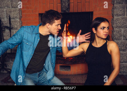 Rude young man angry on young woman. He wave with left hand. Model shows stop sigh. She doesn't want to listen him. They sit at fireplace. - Stock Photo