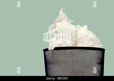 Close up black trash bin with overflowing crumpled paper against a green wall - Stock Photo
