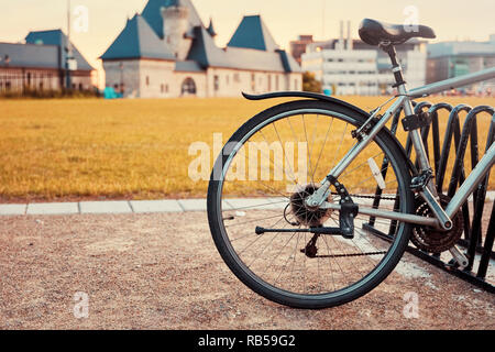 Saddle and back wheel detail of a vintage bicycle parked on a soil road against blurry meadow field and historical building background - Stock Photo