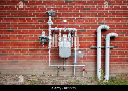 Natural gas meter gauge and pipeline on the red brick wall with copy space - Stock Photo