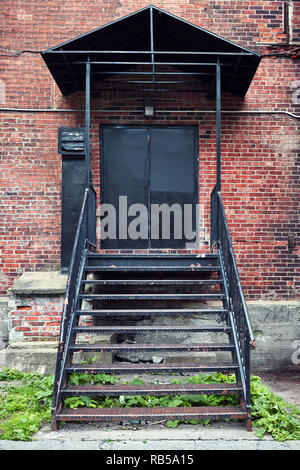 Old red brick industrial building entrance with black iron outer ladder stairs and black metal door. - Stock Photo