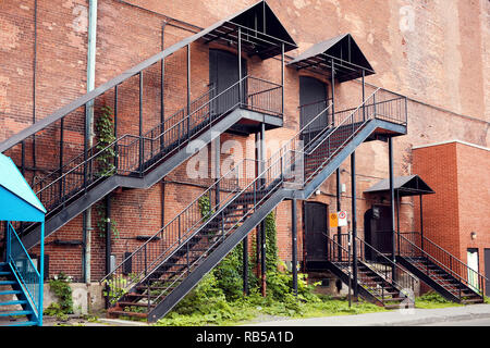Old red brick industrial building facade with black iron outer ladder stairs. - Stock Photo