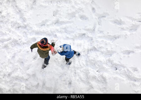 Aerial above view of two little children playing in the snow - Stock Photo