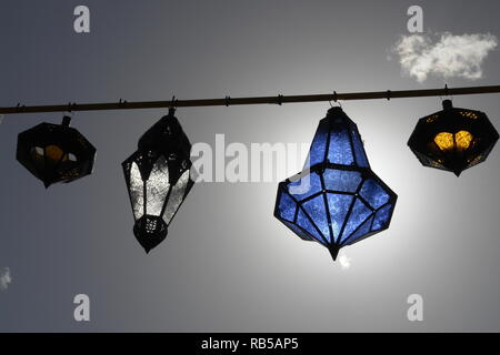 Decorative Muslim lamp against the blue sky and the sun. Symbol of the holy month of Ramadan - Stock Photo