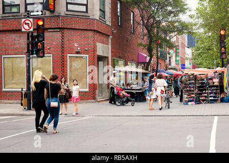 Chinese, afro american and caucasian people crossing the street and shopping in the market at Chinatown in Montreal, Canada. - Stock Photo