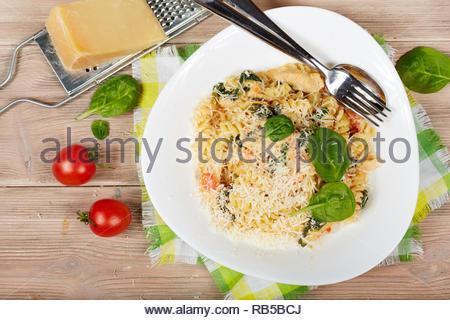 Delicious pasta fusilli with chicken meat, spinach, tomatoes, cream sauce and cheese - Stock Photo