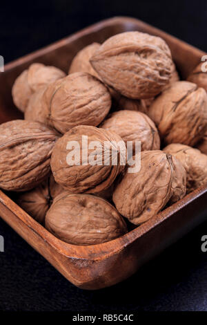 A close up photo of unshelled walnuts in a wooden bowl. - Stock Photo