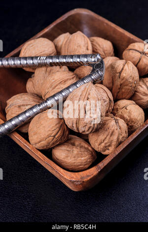 A close up photo of unshelled walnuts and a nutcracker in a wooden bowl. - Stock Photo