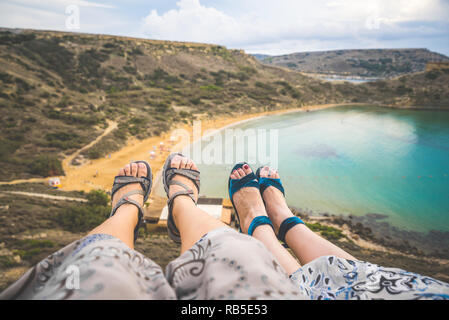 Insta photo of two pair of girls feet on top of a cliff above a beach in Malta - Stock Photo