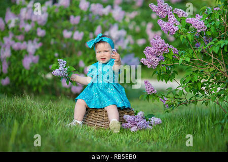 Cute blond baby girl enjoying time on a awesome place between lilac syringe bush.Young lady with basket full of flowers dressed in jeans and stylish s - Stock Photo