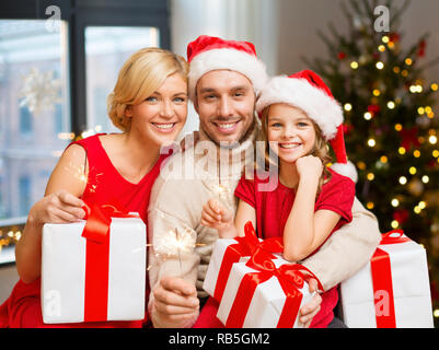 family with christmas gifts and sparklers at home - Stock Photo