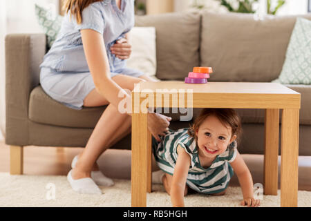 pregnant mother and daughter playing at home - Stock Photo