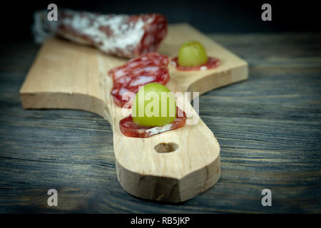 Sliced fresh green grape on slice dry cured Fuet sausage on the handle of a wooden cutting board - Stock Photo