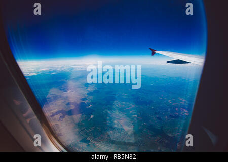 Looking through window aircraft during flight in wing blue sky. - Stock Photo