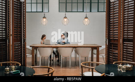 Two young creatives having a meeting in private boardroom in a cafe with laptop - Stock Photo