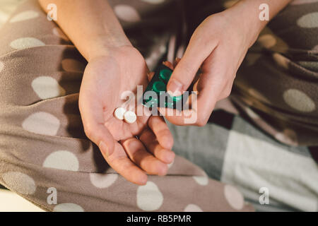 Subject medicine health and pharmaceuticals. Close-up macro young caucasian woman hands pulling out a green blister. Packing two white round pills in home clothes at home on the bed - Stock Photo