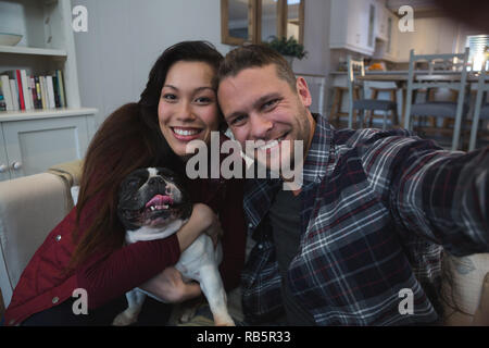 Couple having fun with their pet dog in living room - Stock Photo