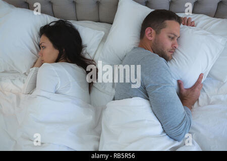 Angry couple avoiding each other in bedroom - Stock Photo