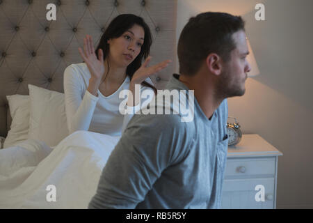 Couple arguing with each other in bedroom - Stock Photo