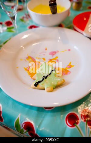 half decorated homemade cookie shaped like a christmas tree, covered with green icing and lying in icing from other efforts on a white plate - Stock Photo