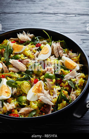 delicious Kedgeree with flaked smoked fish, hard boiled eggs, rice, kale, brussel sprouts, spices and herbs in a dutch oven on a black wooden table, v - Stock Photo