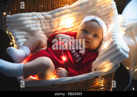 Lovely, beautiful newborn girl lying in basket in a white hat, new year and Christmas decorations, garland on the wall, with a flashlight. card, text. - Stock Photo