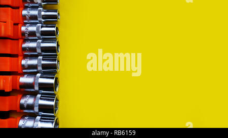 Wrench head bits for the screwdriver and other tools on bright yellow background - Stock Photo