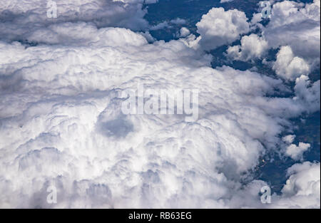 Beautiful view from the window of a plane flying over clouds. Natural panorama with clouds. White clouds moving above the ground. - Stock Photo