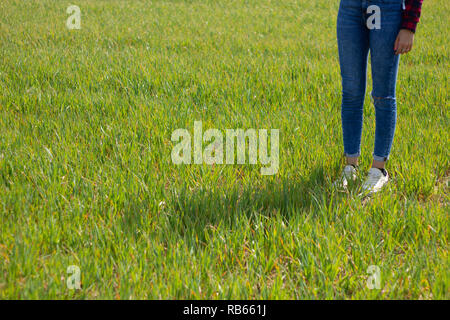 young woman legs in jeans and sneakers with her shadow on the green grass on a sunny day - Stock Photo