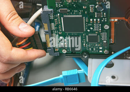 Repairman is connecting the hard disk to the power connector of the desktop computer, close-up. - Stock Photo