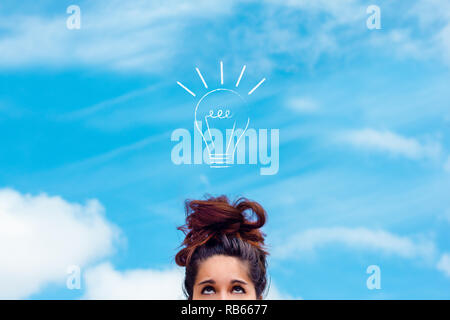 concept of innovation, idea, creativity. Brunette girl with messy bun looking up at a drawn light bulb on the blue sky - Stock Photo