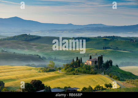 Dawn over Podere Belvedere and the Tuscan countryside near San Quirico d'Orcia, Tuscany, Italy - Stock Photo
