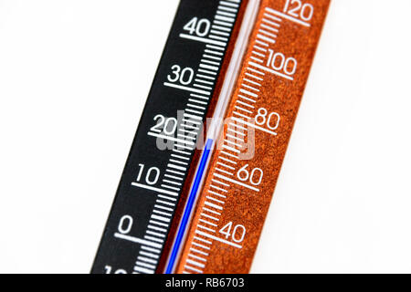 Close-up of a standard wooden room thermometer, marked in degrees Celcius and Fahrenheit, showing a temperature of 22ºC/70ºF - Stock Photo