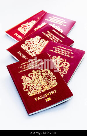 A group of five United Kingdom EU passports isolated on a white background - Stock Photo