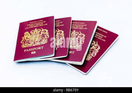 A group of four United Kingdom EU passports isolated on a white background - Stock Photo