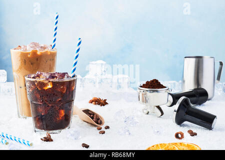 Summer drink iced coffee in a glass and ice coffee with cream in a tall glass surrounded by ice, coffee beans, portafilter, tamper, milk jug and vario