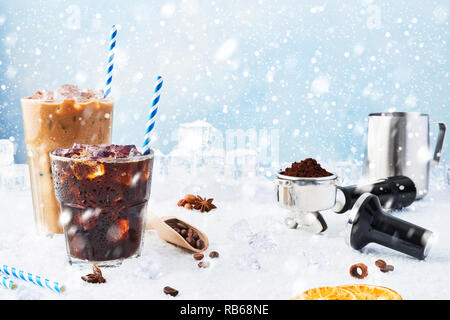 Winter drink iced coffee in a glass and ice coffee with cream in a tall glass surrounded by ice, coffee beans, portafilter, tamper, milk jug and vario