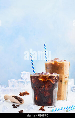 Summer drink iced coffee or soda in a glass and ice coffee with cream in a tall glass surrounded by ice cubes, coffee beans and various spices on snow