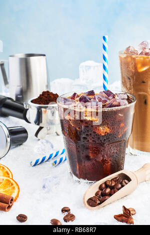 Summer drink iced coffee or soda in a glass and ice coffee with cream in a tall glass surrounded by ice, coffee beans, portafilter, tamper, milk jug a